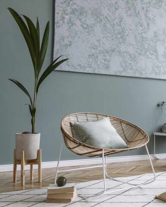 Soft green walls with boho style chair